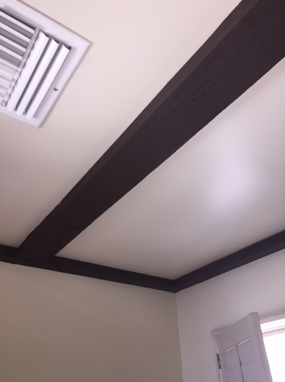 Natural wood beams painted chocolate brown. Seriously?